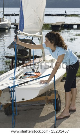 A woman is fixing the ropes on her sail.  She is smiling and looking at the ropes.  Vertically framed shot. - stock photo
