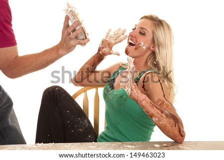 A woman is getting a pie thrown in her face - stock photo
