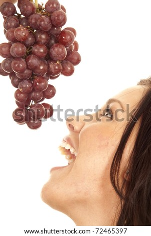 A woman is getting ready to bite into some red grapes. - stock photo