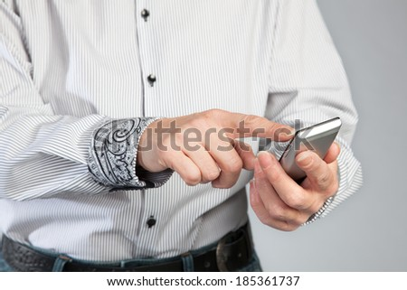 A woman is going to write a message on a smartphone. - stock photo