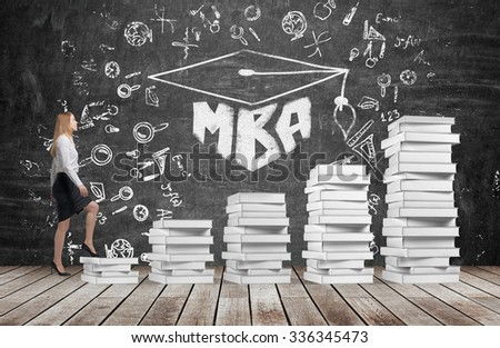 A woman is going up using a stairs which are made of white books to reach graduation hat. The written word MBA is drawn on the black chalkboard which symbolises a professional business education. - stock photo