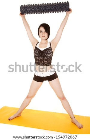 A woman is holding a fitness roll over her head. - stock photo
