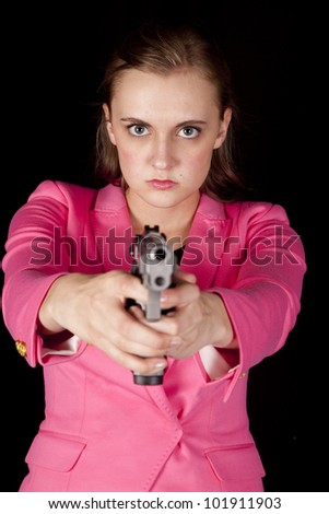 A woman is holding a gun and pointing it. - stock photo