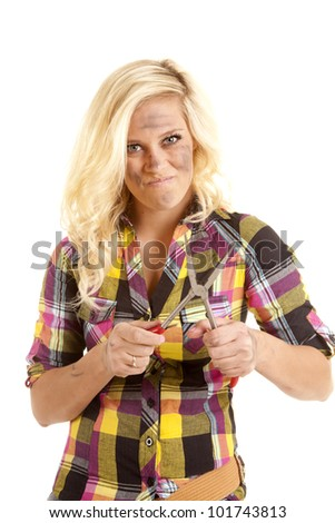 A woman is holding a pair of pliers with a serious look on her face. - stock photo
