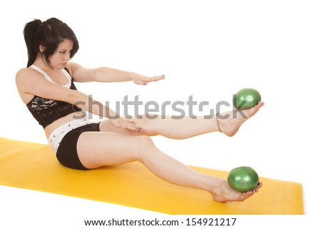 A woman is holding two green balls up on her feet. - stock photo