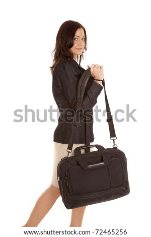 A woman is in a dress and walking with a black bag. - stock photo