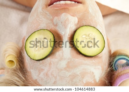A woman is laying with curlers and a cream face mask. - stock photo