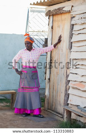 A woman is leaning in front of her home. - stock photo