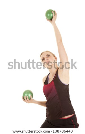 A woman is lifting two medicine balls.  One above her head. - stock photo