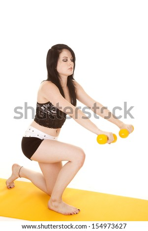 A woman is lunging while  holding yellow weights. - stock photo