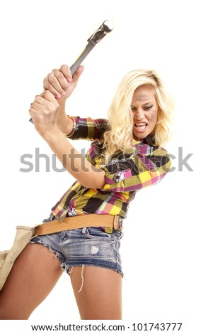 A woman is mad and swinging a hammer to the ground. - stock photo