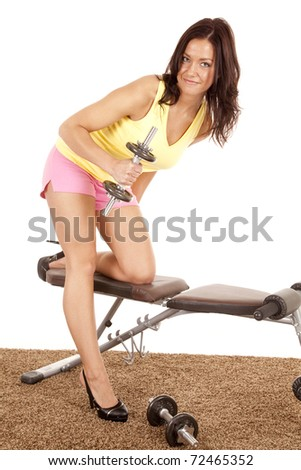 A woman is on a weight bench in heels working out. - stock photo