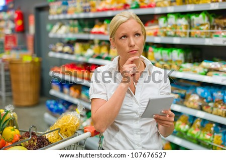 a woman is overwhelmed by the huge selection when shopping in a supermarket. - stock photo