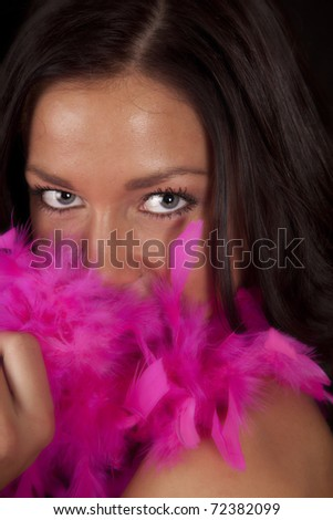 A woman is  peaking out from behind a pink boa. - stock photo