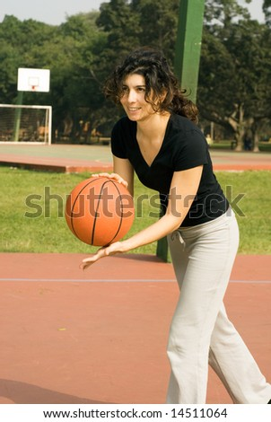 A woman is playing basketball on a park basketball court.  She is smiling and looking away from the camera.  She looks like she is about to dribble the basketball.  Vertically framed photo. - stock photo
