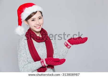 A Woman is presenting something at Chrtstmas, asian - stock photo