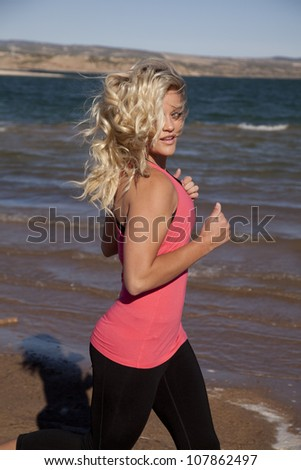 A woman is running on the shoreline by the water looking back - stock photo