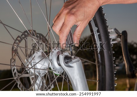 A woman is screwing tightly the fork at her bike. The Bike is in upside down position. - stock photo