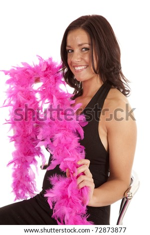 A woman is sitting in a black dress holding a pink boa. - stock photo