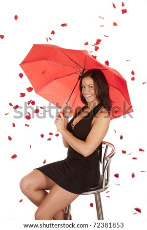 A woman is sitting in a dress with a red umbrella and rose pedals falling all around her. - stock photo