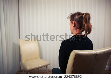A woman is sitting on a chair and is waiting to see her doctor or therapist - stock photo