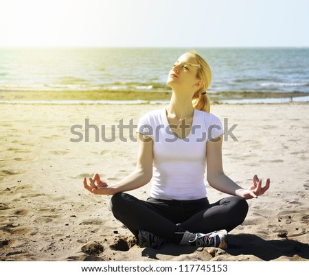 A woman is sitting on the beach with peace and tranquility. She is meditating and there is sunlight in her face. - stock photo