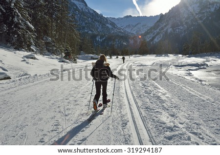 A woman is skiing at the groomed trail in the snowy Marcadau valley. - stock photo