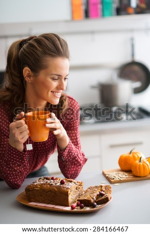 A woman is smiling and relaxing, as she is leaning on the kitchen counter, holding a cup of hot tea. On the counter, a fresh, home-made loaf of pumpkin, cranberry and pumpkin seed bread is ready. - stock photo