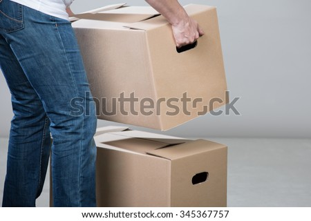 A woman is stacking two heavy cardboxes for a relocation. - stock photo
