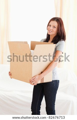 A woman is transporting a filled cardboard - stock photo