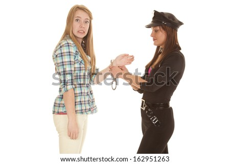 A woman is upset that she is being handcuffed. - stock photo