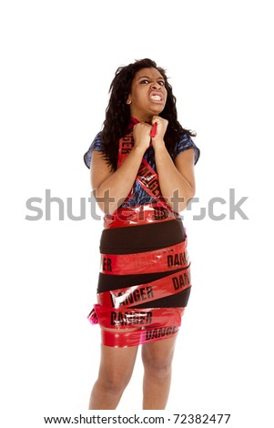 A woman is wrapped in danger tape and looks mad. - stock photo