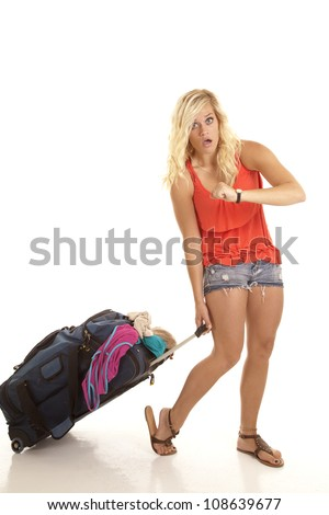 A woman late with her suitcase over packed with clothes falling out of it. - stock photo