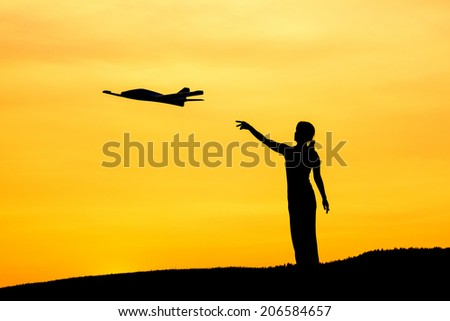A woman launches a toy airplane during a sunset. - stock photo