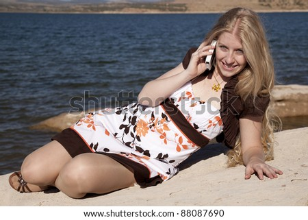 A woman laying in the outdoors by the ocean talking and smiling on the phone. - stock photo