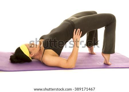 a woman laying on her back with her hips pushed up, stretching - stock photo