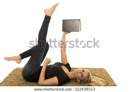 a woman laying on her carpet reading a book with a smile on her face. - stock photo