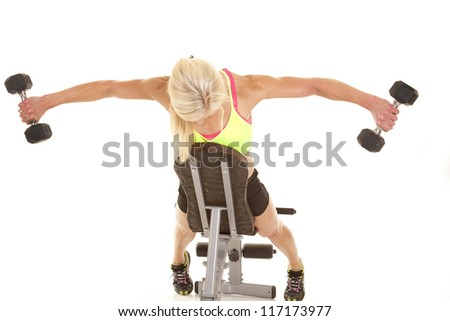 a woman leaning on a bench doing a fly lift with weights. - stock photo