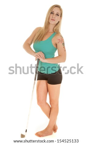 A woman leaning on her golf club with a serious expression on her face. - stock photo