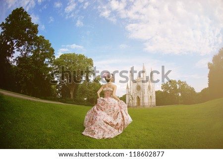 A woman like a princess in an vintage dress before the magic castle - stock photo