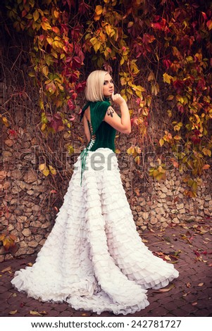 A woman like a princess in an vintage dress in fairy park. Mysterious woman dressed in scenic fashion clothes. Green labyrinth. Model plus - stock photo