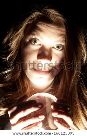 a woman looking and holding on to her crystal ball. - stock photo