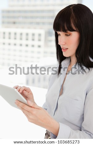 A woman looking at the screen of her tablet pc while in her office - stock photo