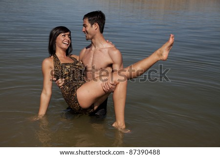 A woman looking in her man's eyes laughing as he holds her up in the air in the water. - stock photo