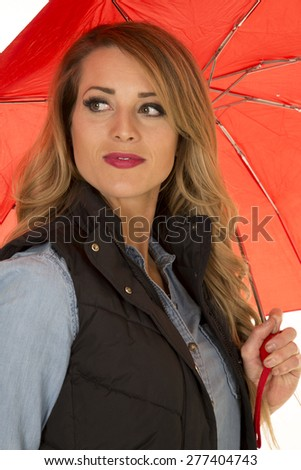 A woman looking over her shoulder holding on to her umbrella. - stock photo
