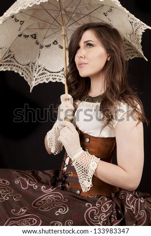 A woman looking up in her vintage western dress while holding on to her umbrella. - stock photo