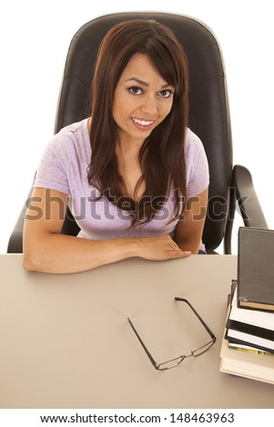 a woman looking up while sitting at her desk with a stack of books smiling - stock photo