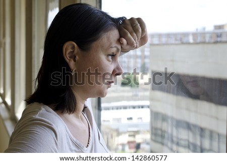 A woman looks out the window - stock photo