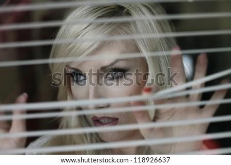 A woman looks through the window cornices - stock photo