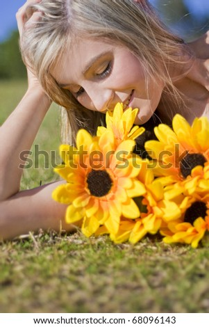 A Woman Lying Down On A Grassy Field Has A Relaxing Rest While Taking Time To Smell The Flowers - stock photo